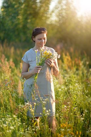 Beuatiful young woman holding wildflowers