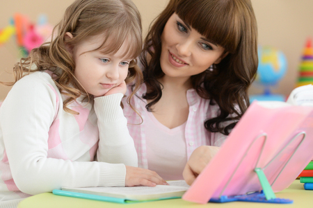 Portrait of mother with daughter doing homework