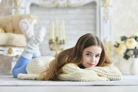 Beautiful teen girl lying on floor in room