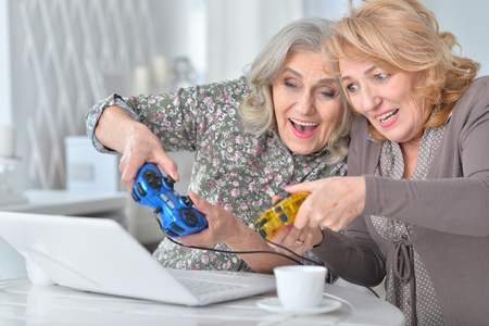 senior women playing computer game with laptop while drinking te