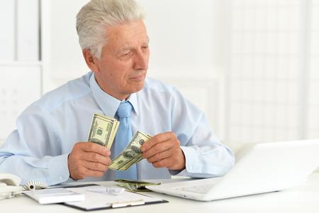 Photo pour Portrait of confident senior businessman holding money - image libre de droit