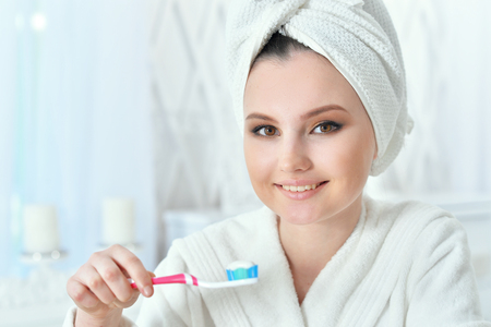 Photo pour Portrait of beautiful young woman with towel on her head brushing teeth in bathroom - image libre de droit
