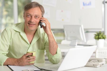 Photo pour Portrait of businessman talking on phone while working with laptop - image libre de droit
