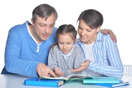 Photo pour Parents with daughter reading books on white background - image libre de droit