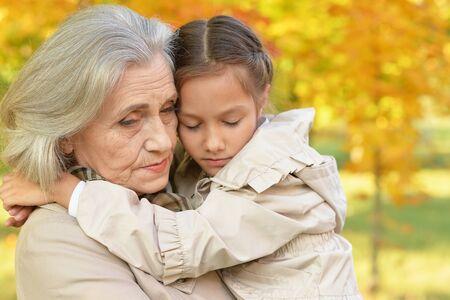 Photo pour Portrait of sad grandmother and granddaughter in park - image libre de droit