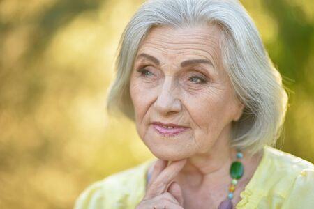 Photo pour Portrait of sad senior beautiful woman in spring park - image libre de droit