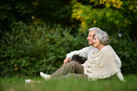 Photo for Portrait of elderly couple sitting on green grass in the summer park - Royalty Free Image