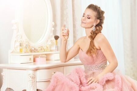Photo pour Portrait of beautiful young woman in pink dress with perfumes - image libre de droit