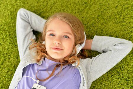 Photo pour Portrait of beautiful teen girl lying on floor - image libre de droit