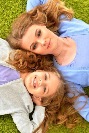 Photo pour Portrait of happy mother with daughter lying - image libre de droit
