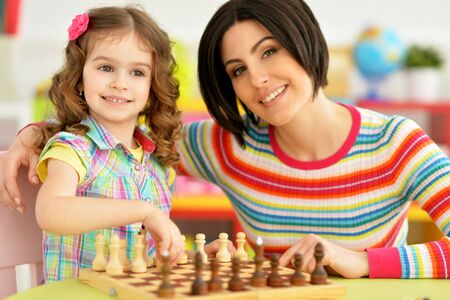 Photo pour Portrait of beautiful young mother with her cute little daughter playing chess - image libre de droit