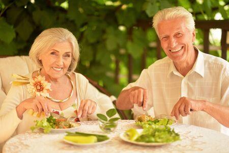 Photo pour Portrait of happy senior couple having diner in the summer park - image libre de droit