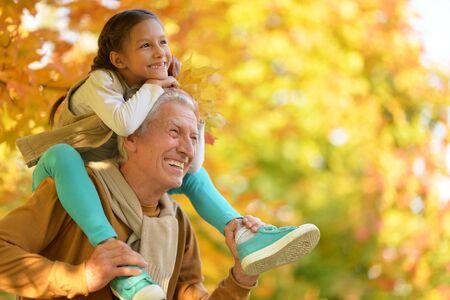 Photo pour Portrait of happy grandfather and granddaughter in park - image libre de droit