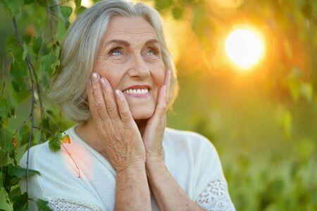 Photo pour Close up portrait of happy senior woman in park - image libre de droit