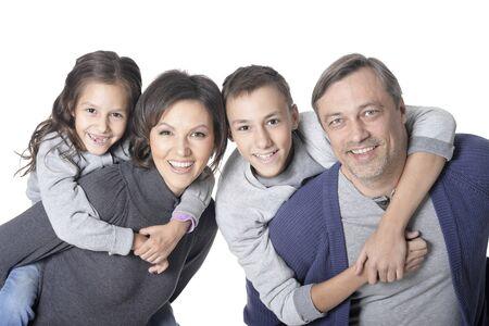 Photo pour Portrait of happy smiling family of four posing together on white - image libre de droit