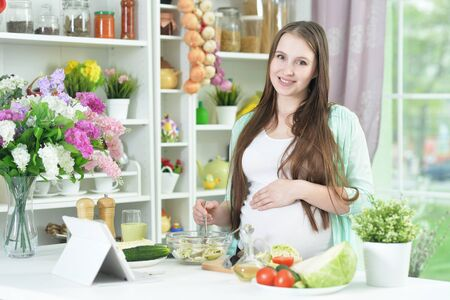Photo for Beautiful pregnant young woman cooking in kitchen - Royalty Free Image