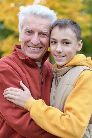 Photo pour Portrait of happy grandfather and grandson in park - image libre de droit
