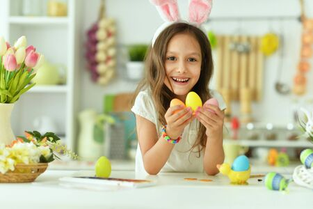 Photo pour Beautiful girl in bunny ears painting eggs for Easter holiday - image libre de droit