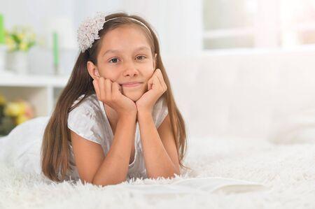 Photo pour Close up portrait of little cute girl reading book at home - image libre de droit