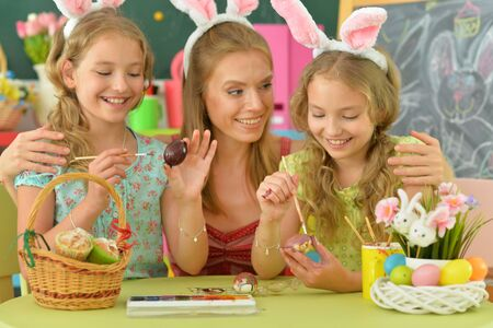 Photo pour Mother with daughters wearing rabbit ears decorating Easter eggs - image libre de droit