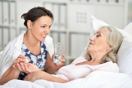 Photo pour Senior woman in hospital with caring daughter - image libre de droit