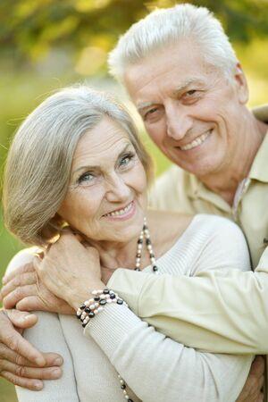 Photo pour Smiling senior couple embracing in autumn park - image libre de droit
