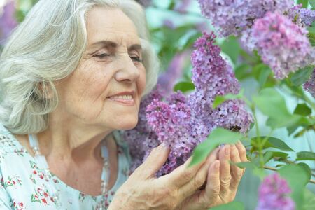 Close-up portrait of happy senior beautiful woman on lilacs background