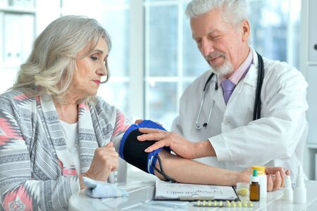 Photo pour Portrait of elderly doctor measuring blood pressure - image libre de droit