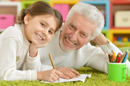Photo pour Portrait of happy grandfather with granddaughter drawing together - image libre de droit