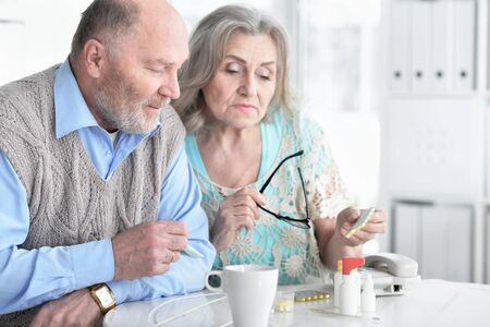 Photo pour Ill senior woman with pills while husband sitting nearby - image libre de droit