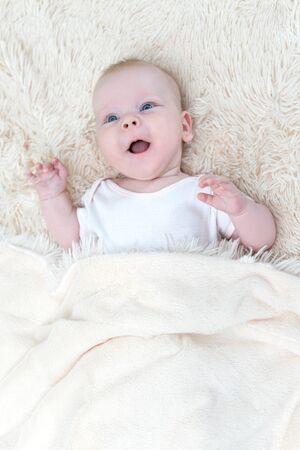 Photo pour Cute little baby girl lying under the blanket - image libre de droit