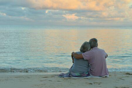 Photo pour Back view. Happy elderly couple resting on tropical beach - image libre de droit