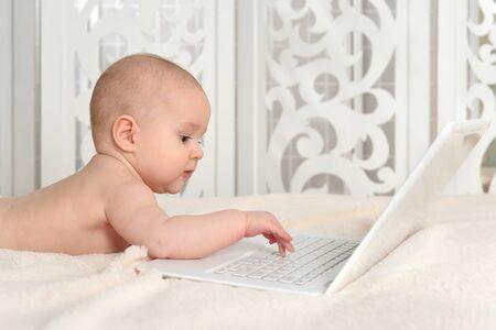 Foto für Cute little baby boy on bed with laptop - Lizenzfreies Bild