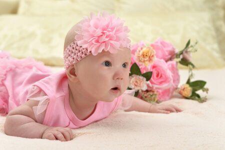 Photo pour Cute little baby girl on bed with flowers - image libre de droit