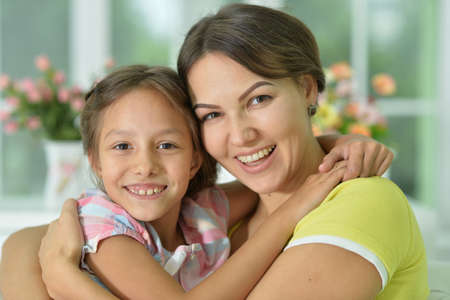 Photo pour Portrait of a charming little girl hugging with mom at home - image libre de droit