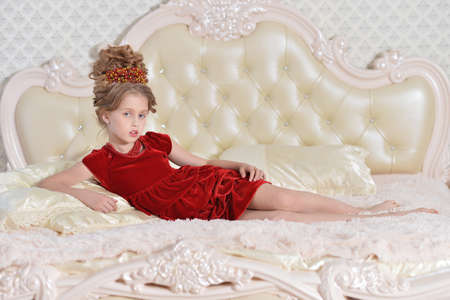 Photo pour Cute little girl in red dress lying on bed - image libre de droit