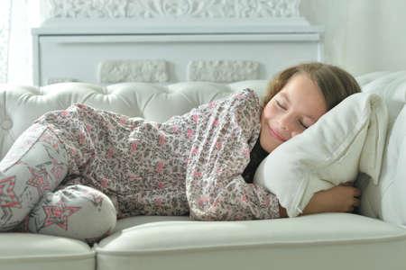 Photo pour Portrait of cute little girl sleeping on sofa - image libre de droit