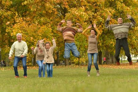 Photo pour Happy smiling family relaxing in autumn park jumping - image libre de droit