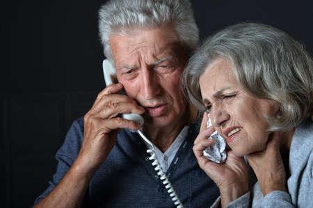 Photo pour Portrait of sick elderly woman and man calling doctor - image libre de droit