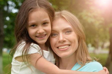 Photo pour Portrait of mother and daughter hugging outdoors - image libre de droit