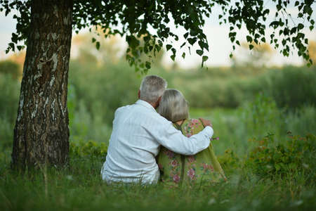 Photo for Back view of senior couple sitting on grass - Royalty Free Image