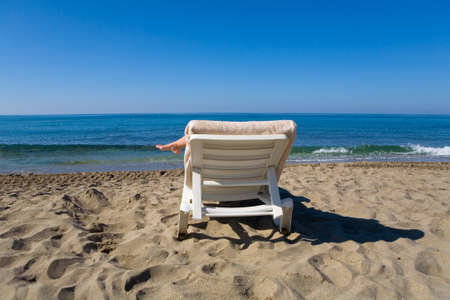 A man is resting on a deckchair by the sea. Beach vacation.