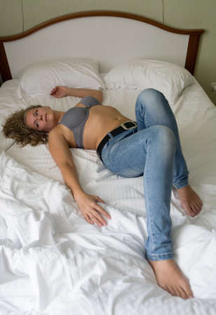 Photo pour Beautiful mature blonde in bra is lying on the bed. People. - image libre de droit