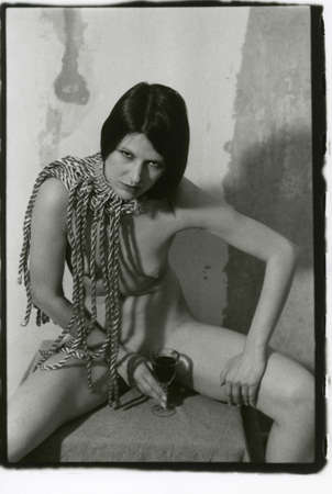 Foto de Young beautiful girl with naked breasts and a glass of wine in her hand. Attention! Image contains grit and other artifacts of analog photography! - Imagen libre de derechos