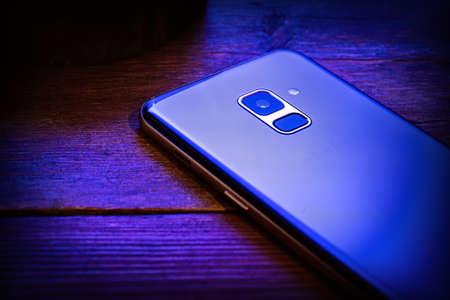 Photo pour blue mobile phone on a wooden background - image libre de droit