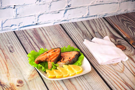 Photo pour Two grilled pink salmon steaks lie on a white ceramic plate decorated with lemon slices and a lettuce leaf next to a white napkin with cutlery, the whole composition on a wooden table. Close-up. - image libre de droit