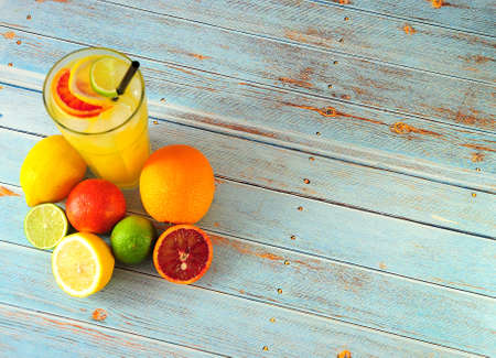 Photo pour A tall glass cup of citrus juice with ice and a straw, stands on a table in a pile of whole and chopped oranges, lemons, lime and a small grapefruit. Close up shot. - image libre de droit
