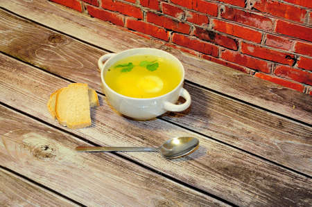 Photo pour Deep round plate with handles of fresh chicken broth with egg, spoon and two slices of white bread on a wooden table against a red brick wall. Close-up. - image libre de droit