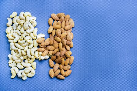 Capital letter H from almonds and cashew on blue background.