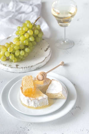 Photo pour Camembert with honey, grapes and glass of white wine - image libre de droit